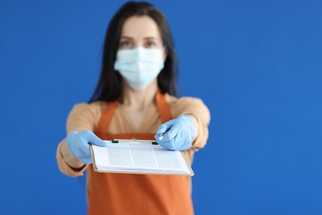 ドキュメントとペンのクローズアップでクリップボードを与える保護マスクと手袋の女性宅配便
