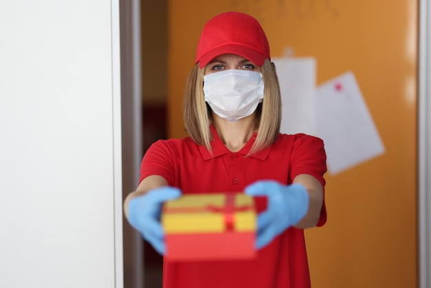 Woman courier in protective medical mask and gloves giving gift
