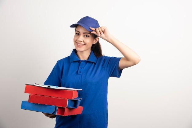 ピザとクリップボードの段ボールを持つ女性宅配便。高品質の写真