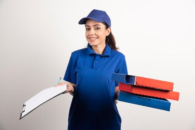 Corriere donna con cartone di pizza e appunti. foto di alta qualità