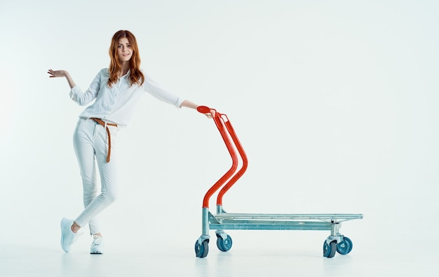 Woman courier with cargo trolley on light