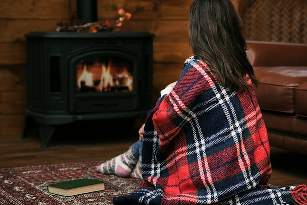 Woman covered in blanket next to fireplace