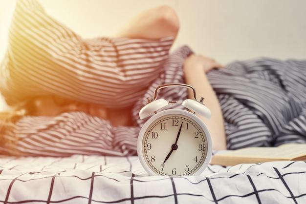 女性は目覚まし時計から保護するために枕で耳を覆った