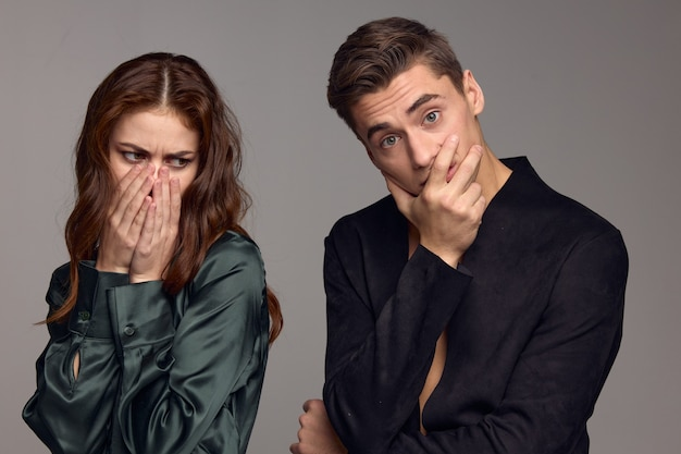 The woman covered her mouth with her hands and turned away from the surprised man. high quality photo