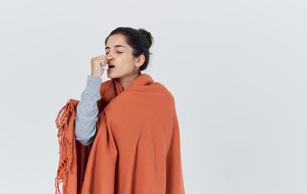 女性は毛布の冷たい鼻水インフルエンザの健康問題で身を覆った
