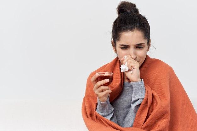 お茶の健康問題を飲んで家で毛布で覆われた女性