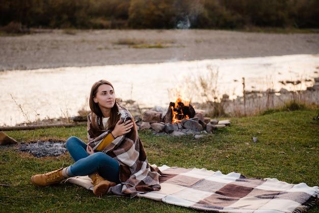 毛布をかぶった女性が川辺で焚き火を楽しむ