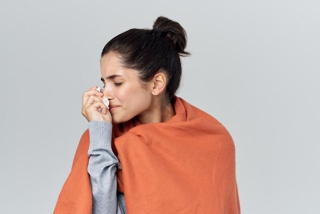 Укрытая одеялом женщина вытирает нос платком простуды