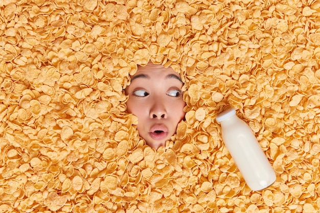 Woman covered with cornflakes bottle of fresh milk feels excited has scared shocked expression