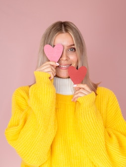 Woman covering eye with paper heart