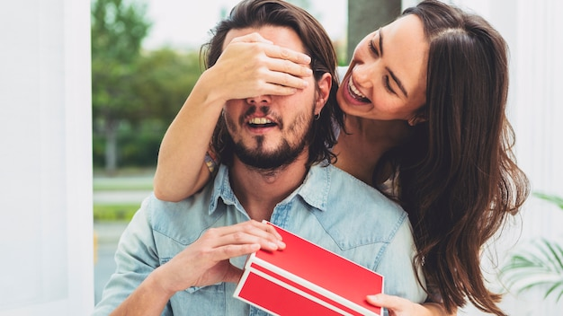 Woman covering eyes of man with gift box