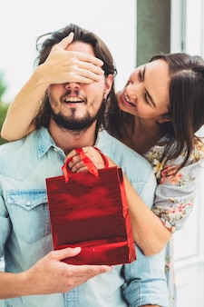 Woman covering eyes of man with red gift bag