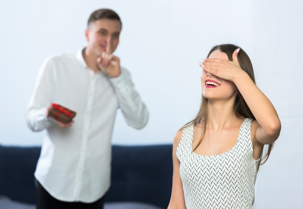 Woman covering eyes waiting man with gift