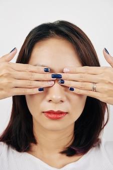 Женщина, закрывающая глаза руками