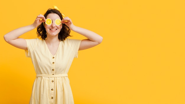 Woman covering eyes with lemon slices