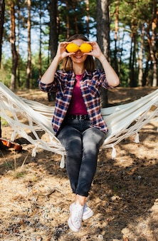 Woman covering eyes with lemons
