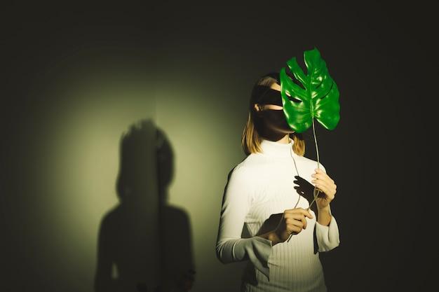 큰 녹색 잎으로 얼굴을 덮고 여자
