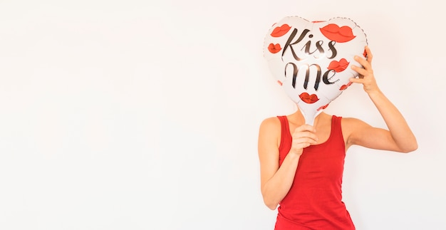 Woman covering face with big heart balloon