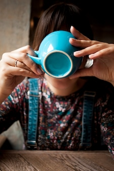 Woman covering face with blue ceramic cup while drinking coffee