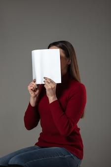 灰色の壁で読んでいる間、本で顔を覆っている女性。祝う、教育、芸術、新しいキャラクターのコンセプトを楽しむ。