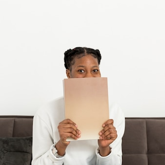 Woman covering face with book
