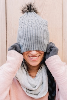 Woman covering face with cap
