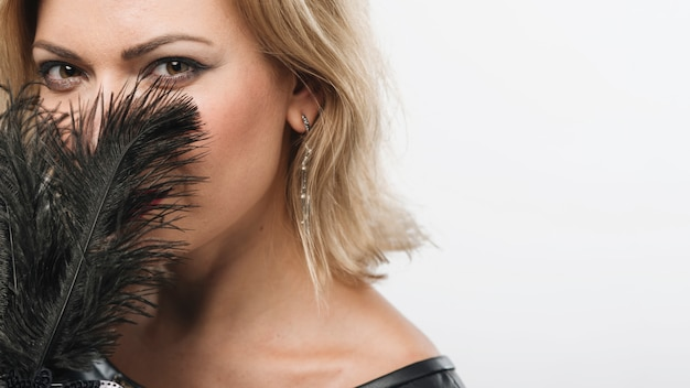 Woman covering face with feathers of mask