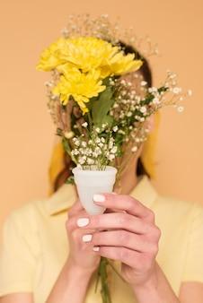 플라스틱 컵에 꽃으로 얼굴을 덮고 여자