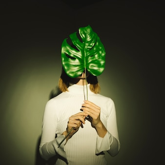 Woman covering face with green leaf