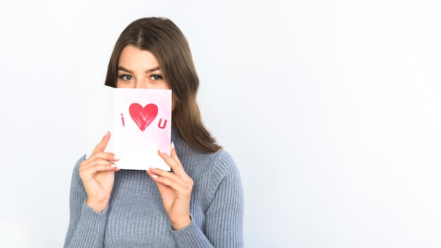 Woman covering face with greeting card