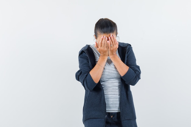 Женщина закрыла лицо руками в футболке
