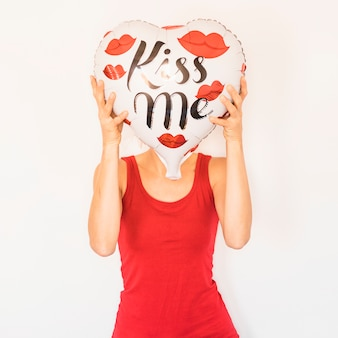 Woman covering face with heart balloon
