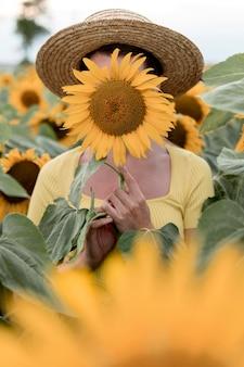 ひまわりで顔を覆っている女性