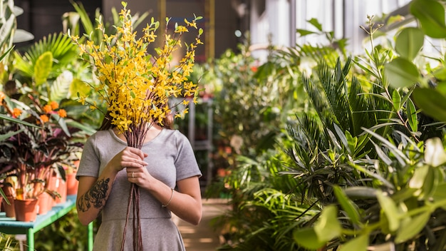 Woman covering face with yellow flowers bouquet