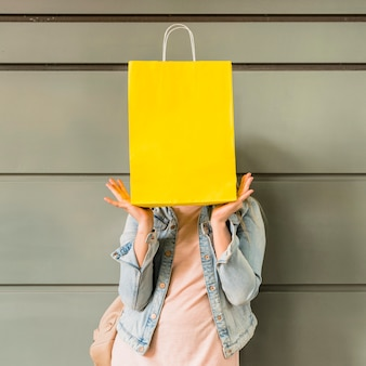 Woman covering face with yellow shopping bag
