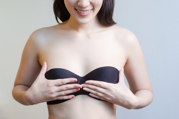 Woman covering her breast with hands while standing isolated on background