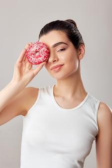 흰색 배경에 흰색 탱크 탑에 도넛으로 그녀의 눈을 덮고있는 여자