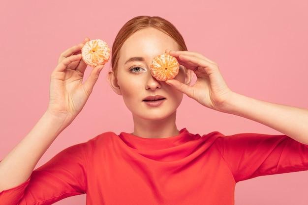 Женщина закрыла глаза апельсинами