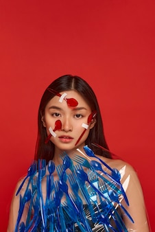 Женщина закрыла лицо и тело красной и синей пластиковой посудой с копией пространства