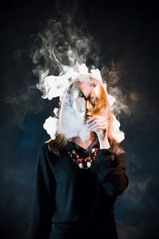 니코틴 연기로 둘러싸인 마스크로 얼굴을 가리는 여성. 수동 흡연 개념의 위험