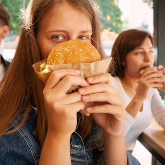 Woman covering her face with burger