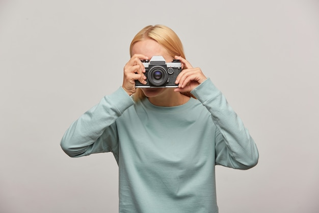 Woman covering her face with the camera making a photo session