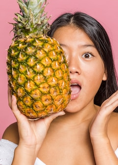 Woman covering her face with full size pineapple