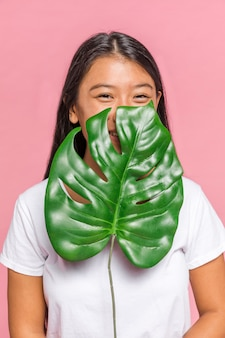 Woman covering her face with monstera leaf