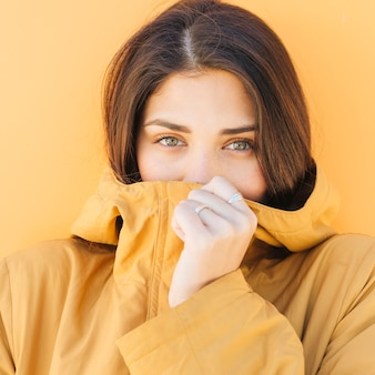 Woman covering her mouth with jacket looking at camera