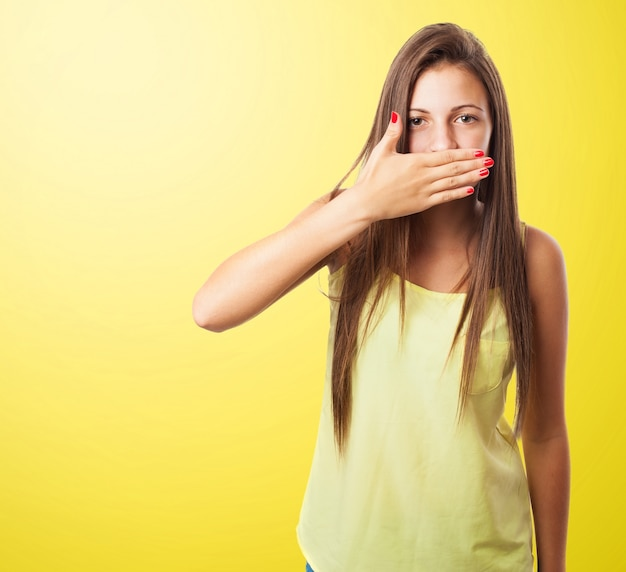 Woman covering her mouth in a yellow background
