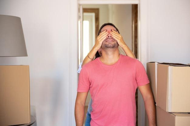 남자 친구의 눈을 손으로 가리고 카톤 상자가있는 새 아파트로 인도하는 여성