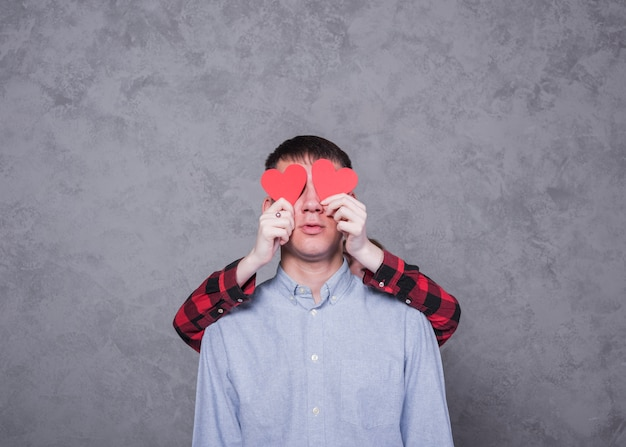 Woman covering man eyes with red paper hearts