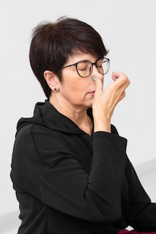 Woman covering a nostril with her finger