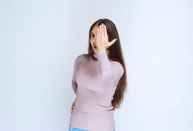 顔の一部を覆い、片目で見ている女性。